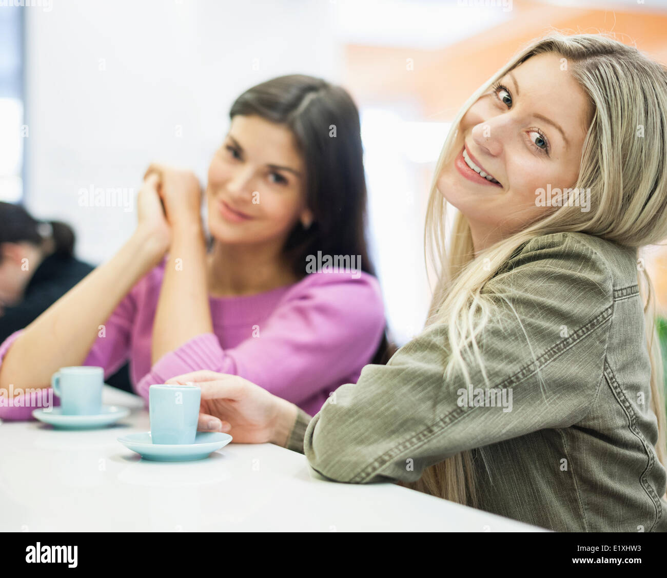 Portrait of young businesswomen smiling at cafeteria table - Stock Image