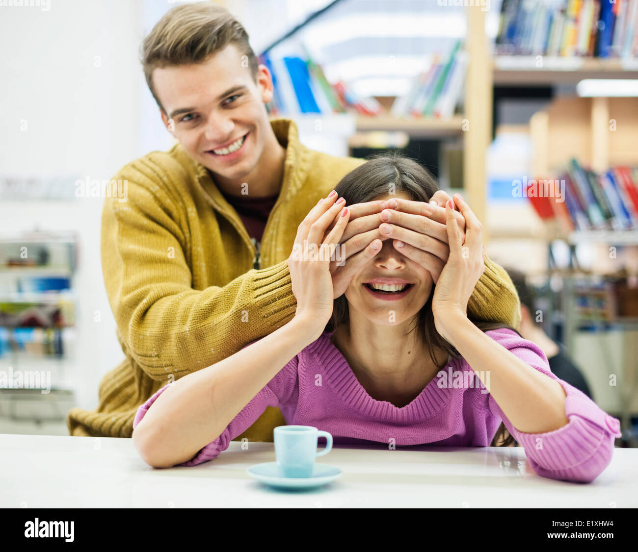 Playful young man covering woman's eyes in library - Stock Image