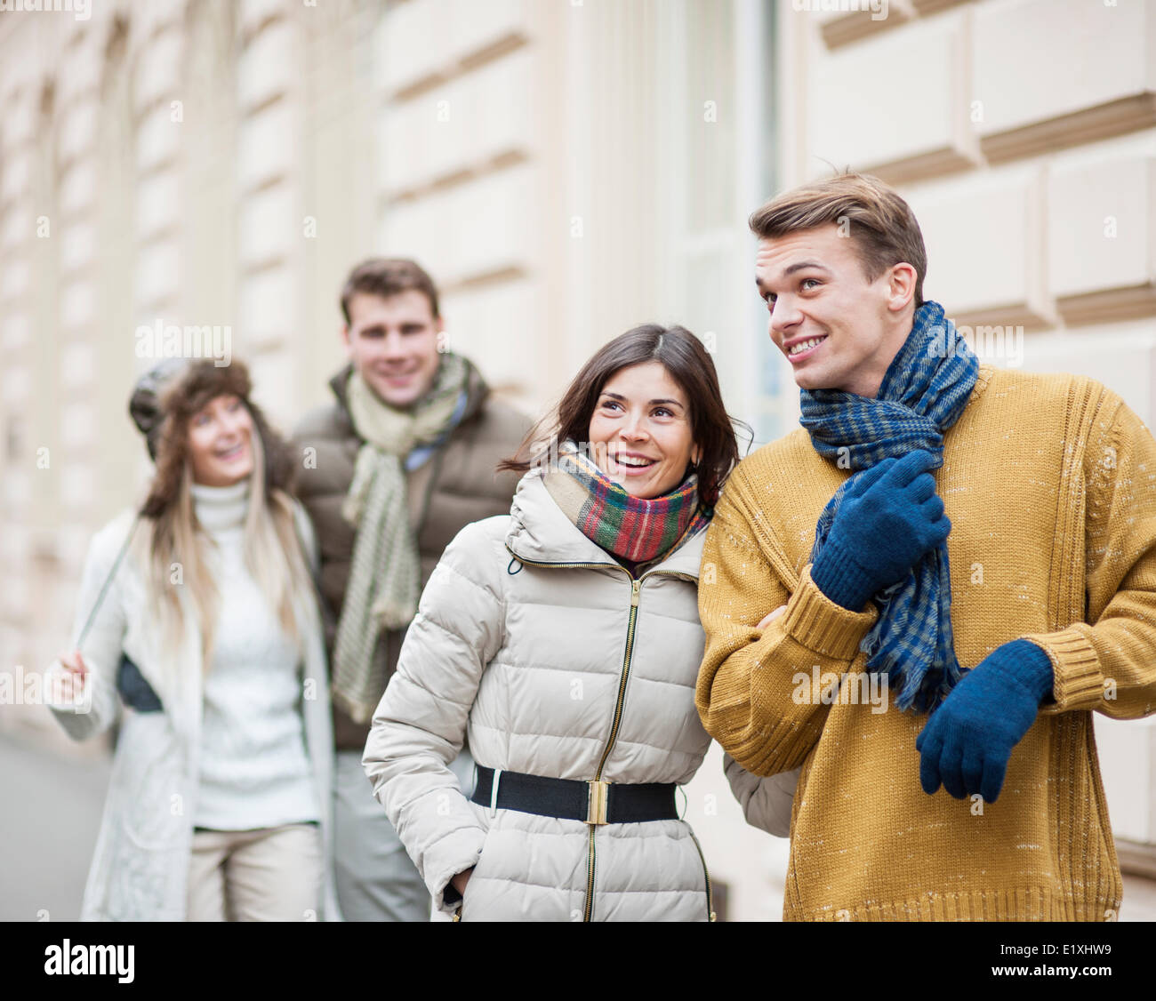 Happy young couples in warm clothing enjoying vacation - Stock Image