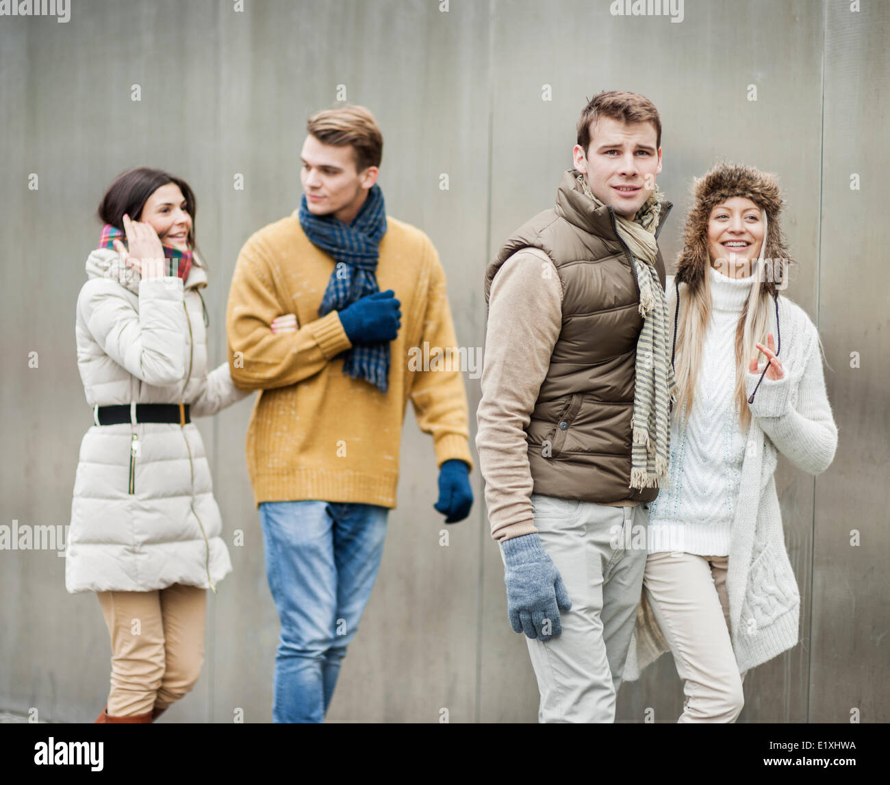 Smiling young couples walking against wall - Stock Image
