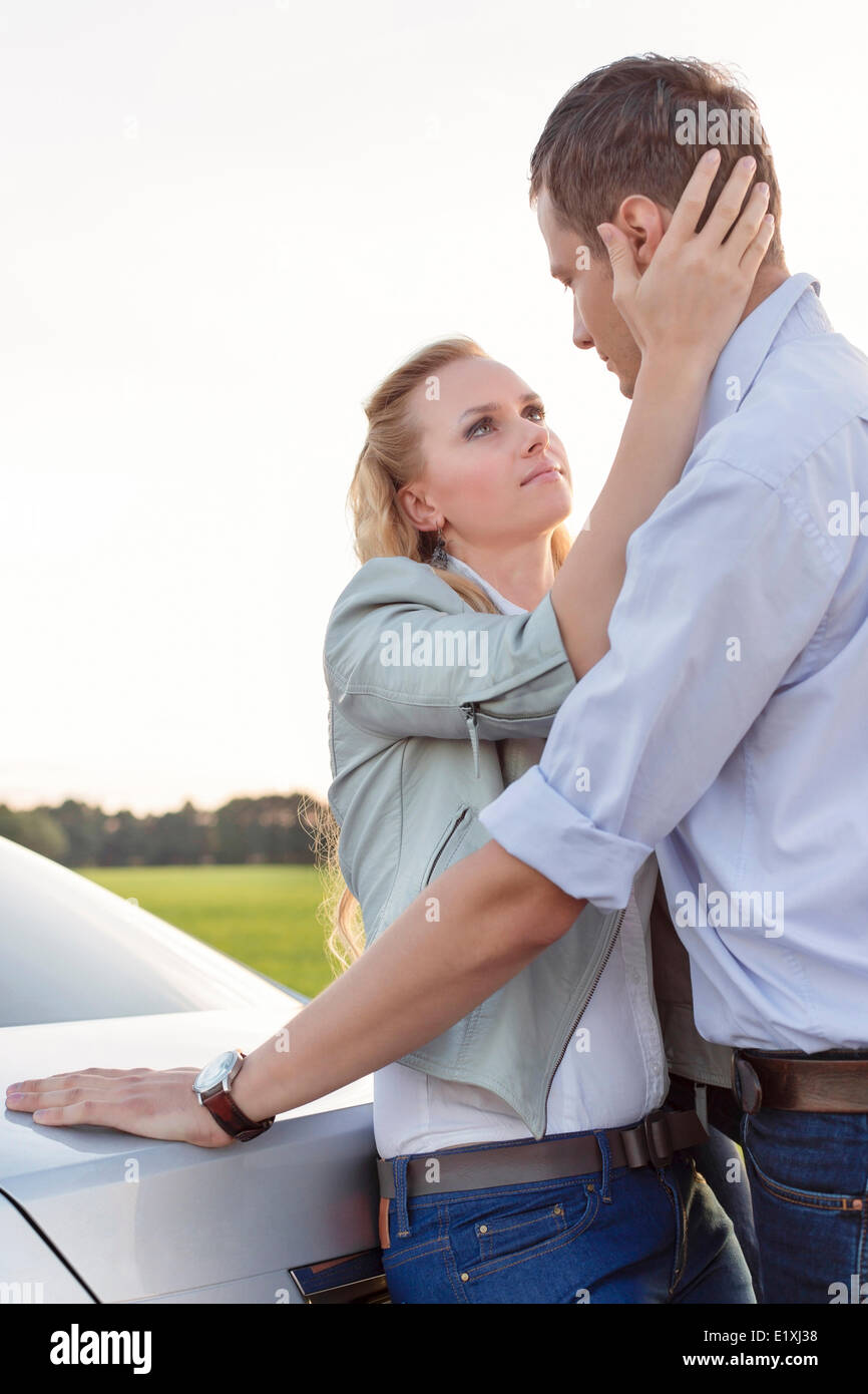 Side view of romantic young couple by car at countryside - Stock Image