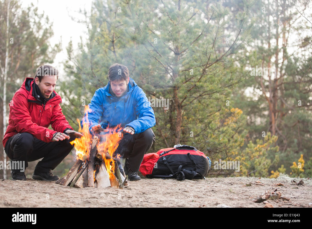 Male backpackers warming hands at campfire in forest - Stock Image