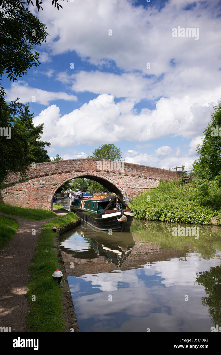 Narrowboat going under a bridge on the Grand Union Canal at Braunston, Northamptonshire, England - Stock Image
