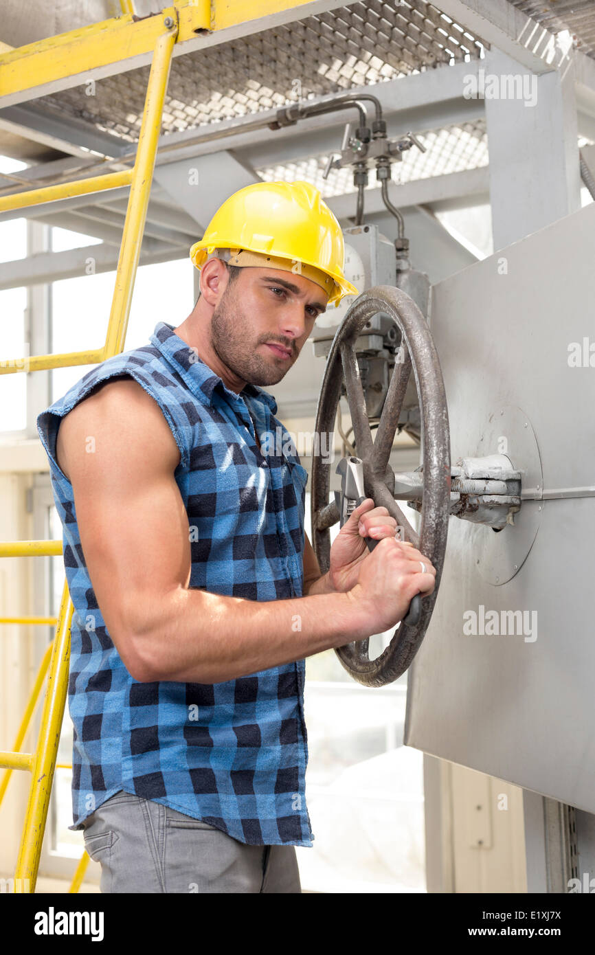 Young worker fixing industrial valve with wrench - Stock Image