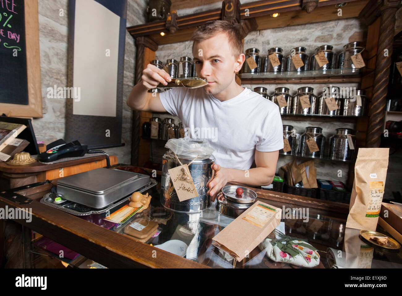 Salesman smelling tea in store - Stock Image