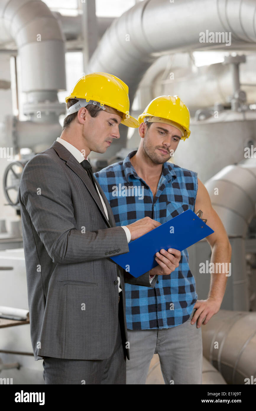 Manual worker with supervisor discussing over clipboard in industry - Stock Image
