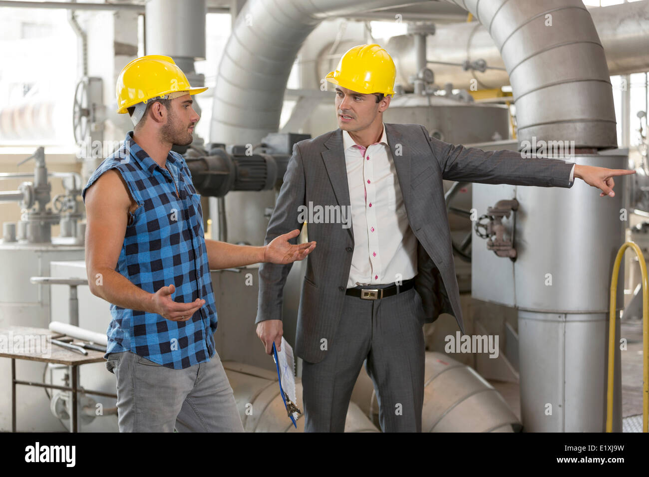 Serious manager showing something to worker in industry - Stock Image