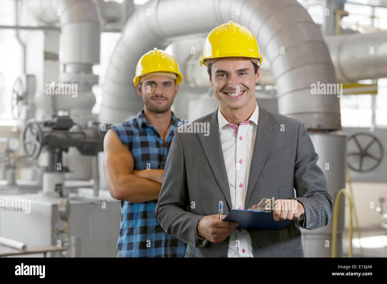 Portrait of young male supervisor holding clipboard with manual worker in background at industry - Stock Image