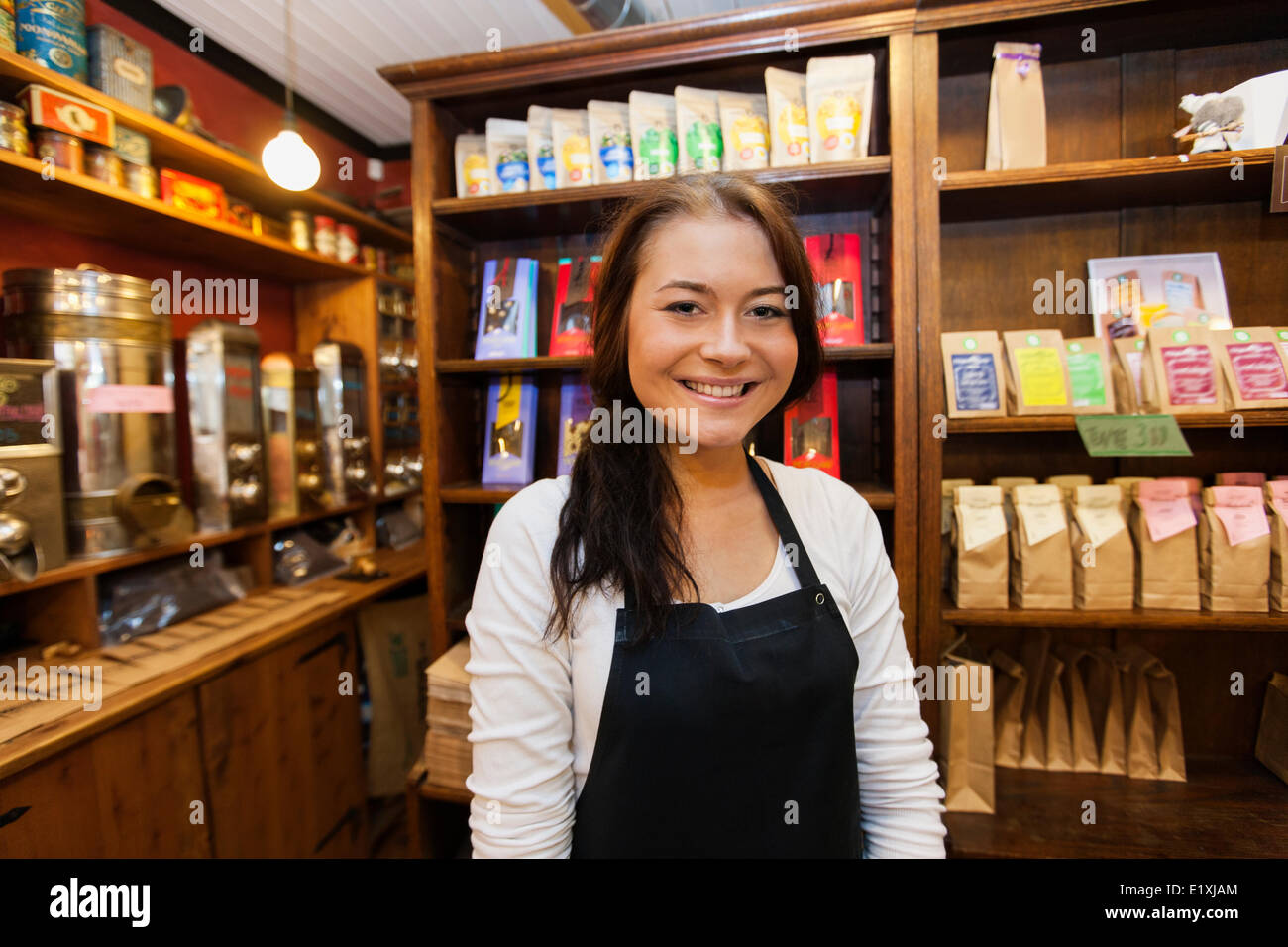 Portrait of female salesperson smiling in coffee shop Stock Photo