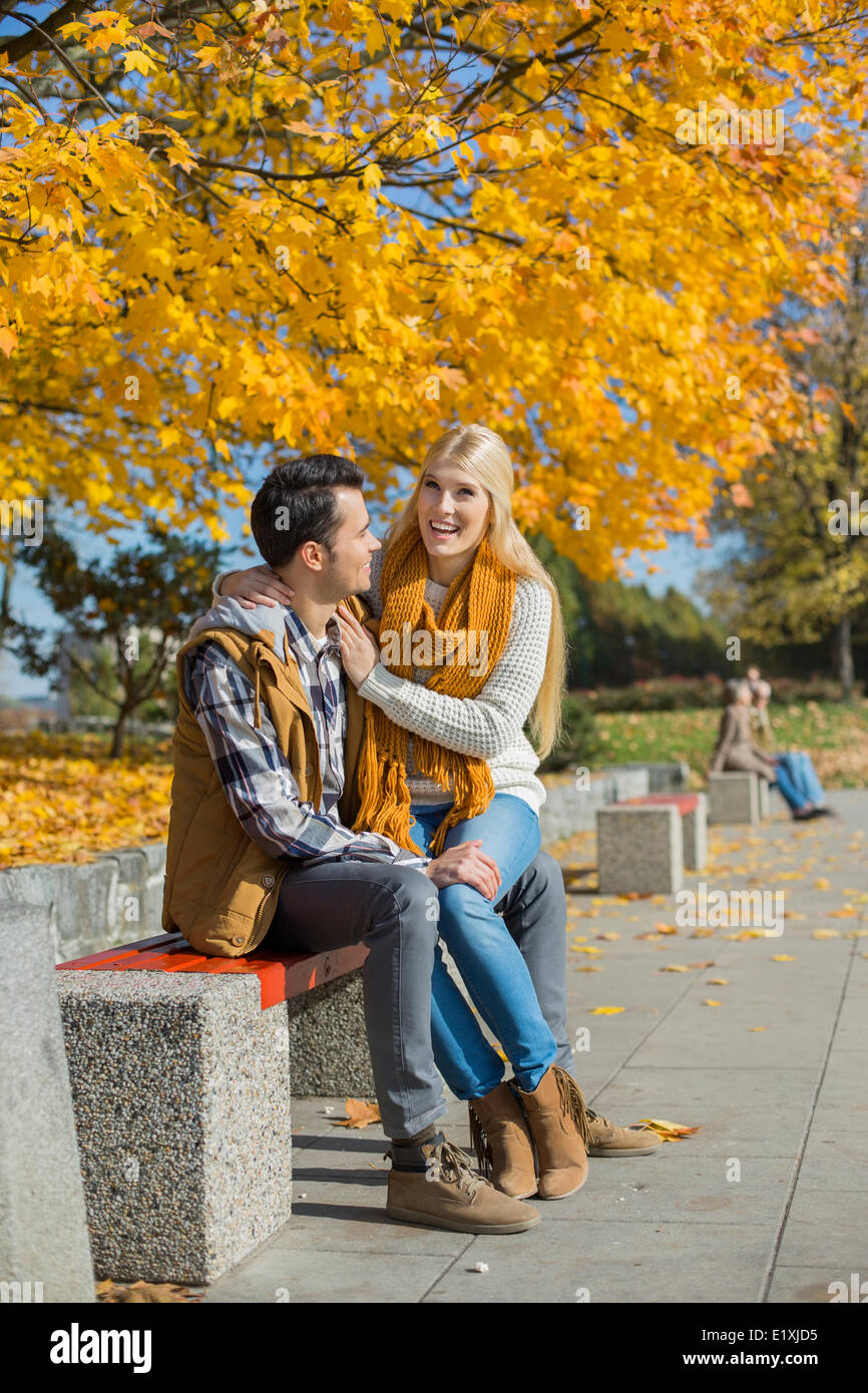 Happy woman sitting on man's lap at park during autumn - Stock Image