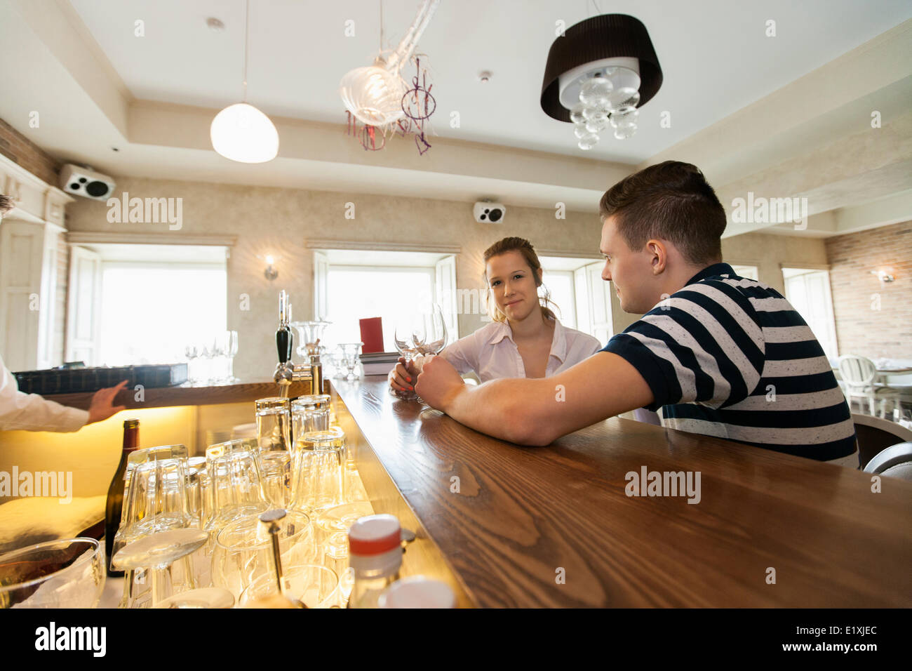 Portrait of young woman sitting with man at bar counter - Stock Image