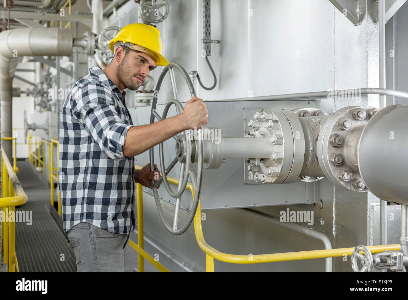 Industrial worker turning large valve - Stock Image