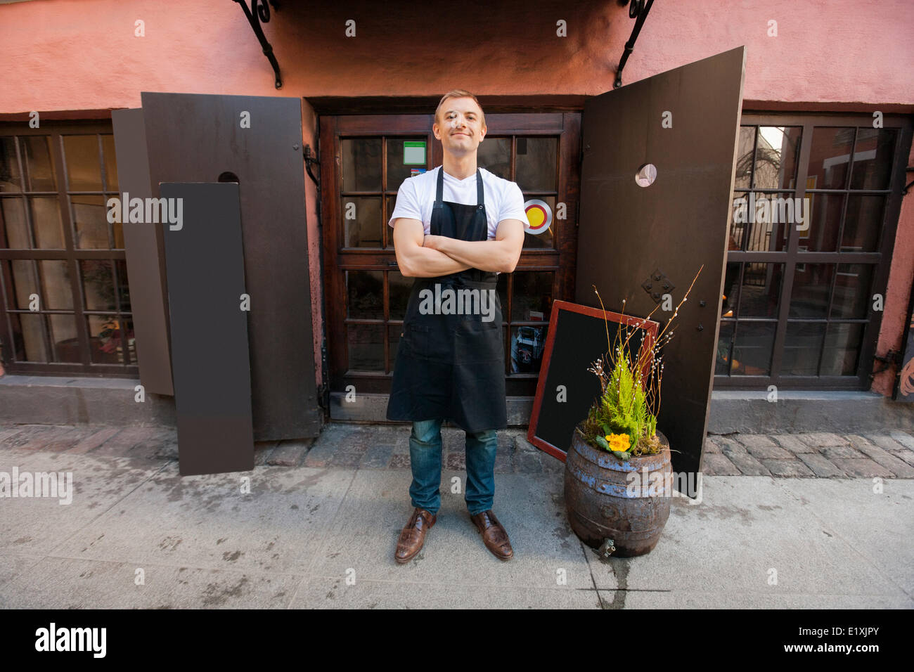 Portrait of confident male salesperson standing arms crossed outside coffee store - Stock Image