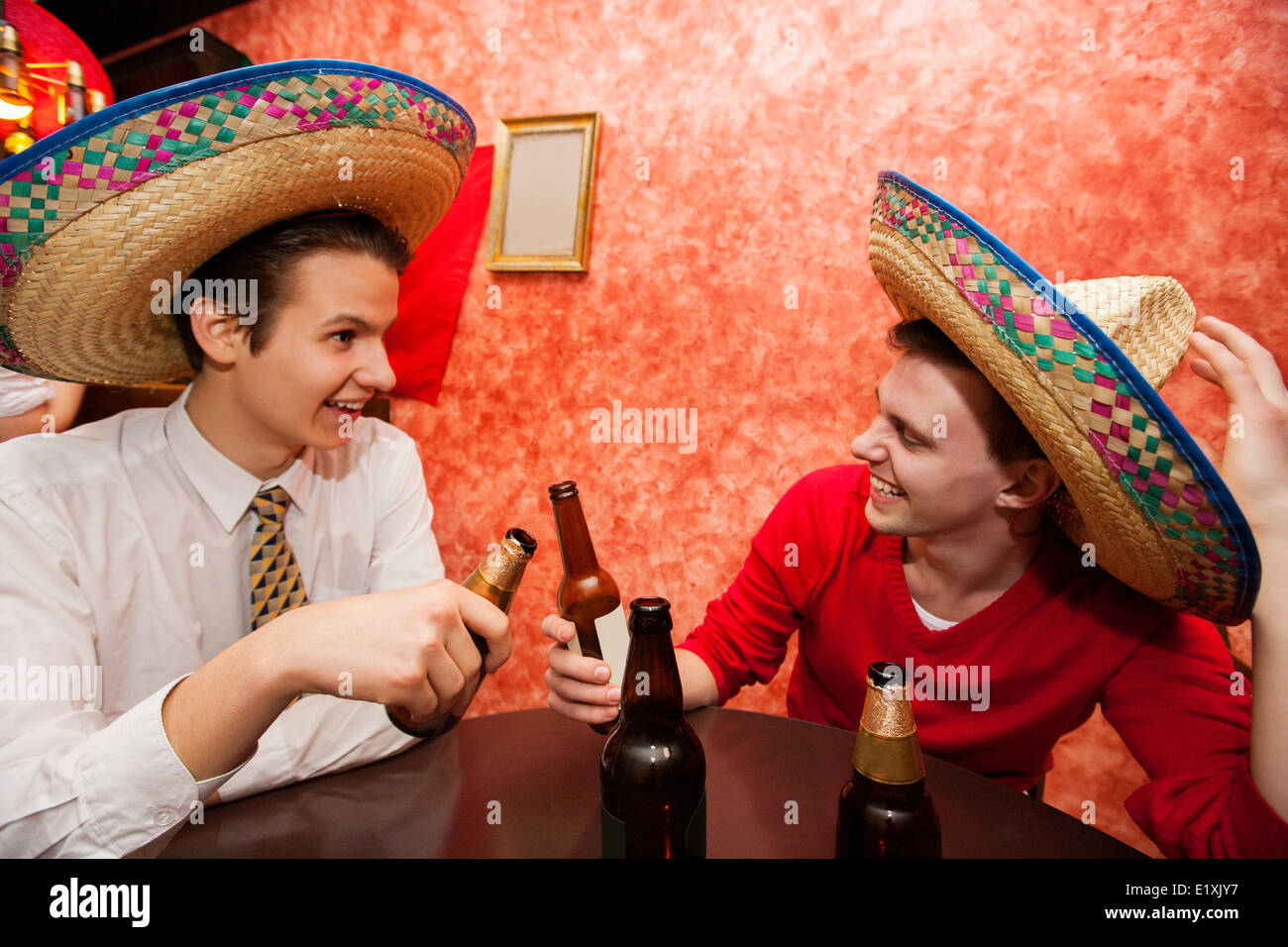Happy friends wearing Mexican hats toasting at restaurant table - Stock Image