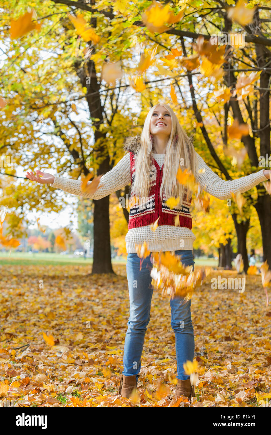 Autumn leaves falling on young woman with arms outstretched in park - Stock Image