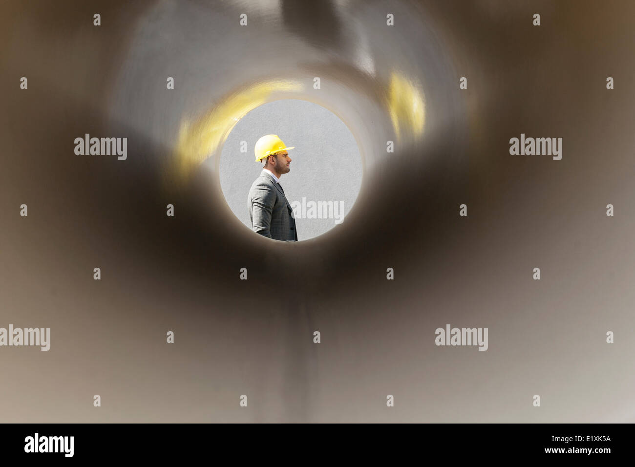 Side view of young male architect through large pipe at construction site - Stock Image