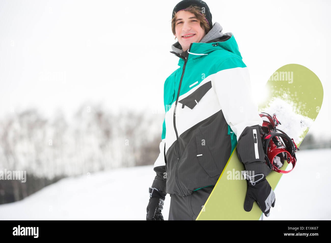 Portrait of handsome young man with snowboard in snow - Stock Image