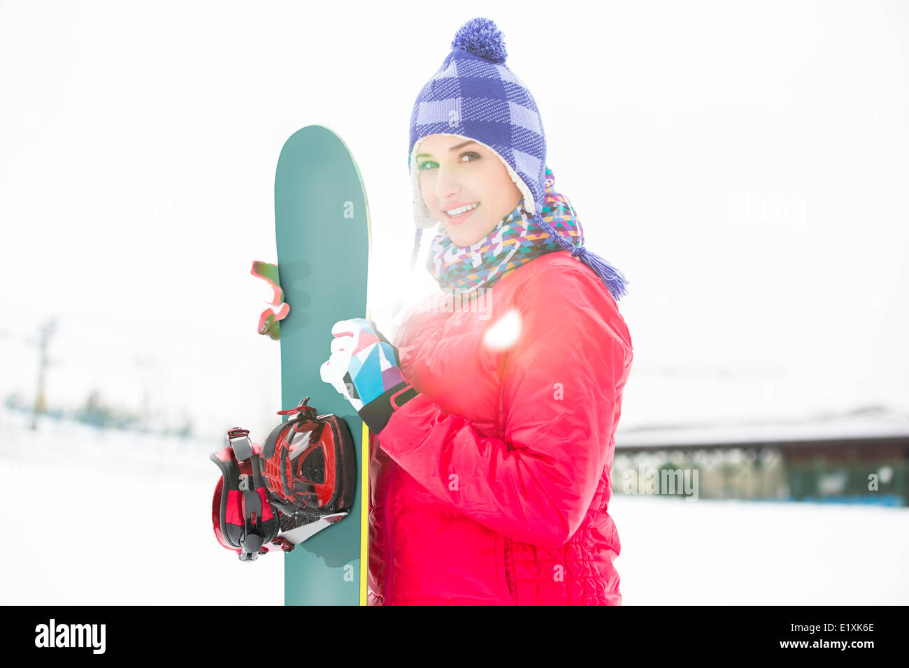 Portrait of beautiful young woman holding snowboard in snow - Stock Image