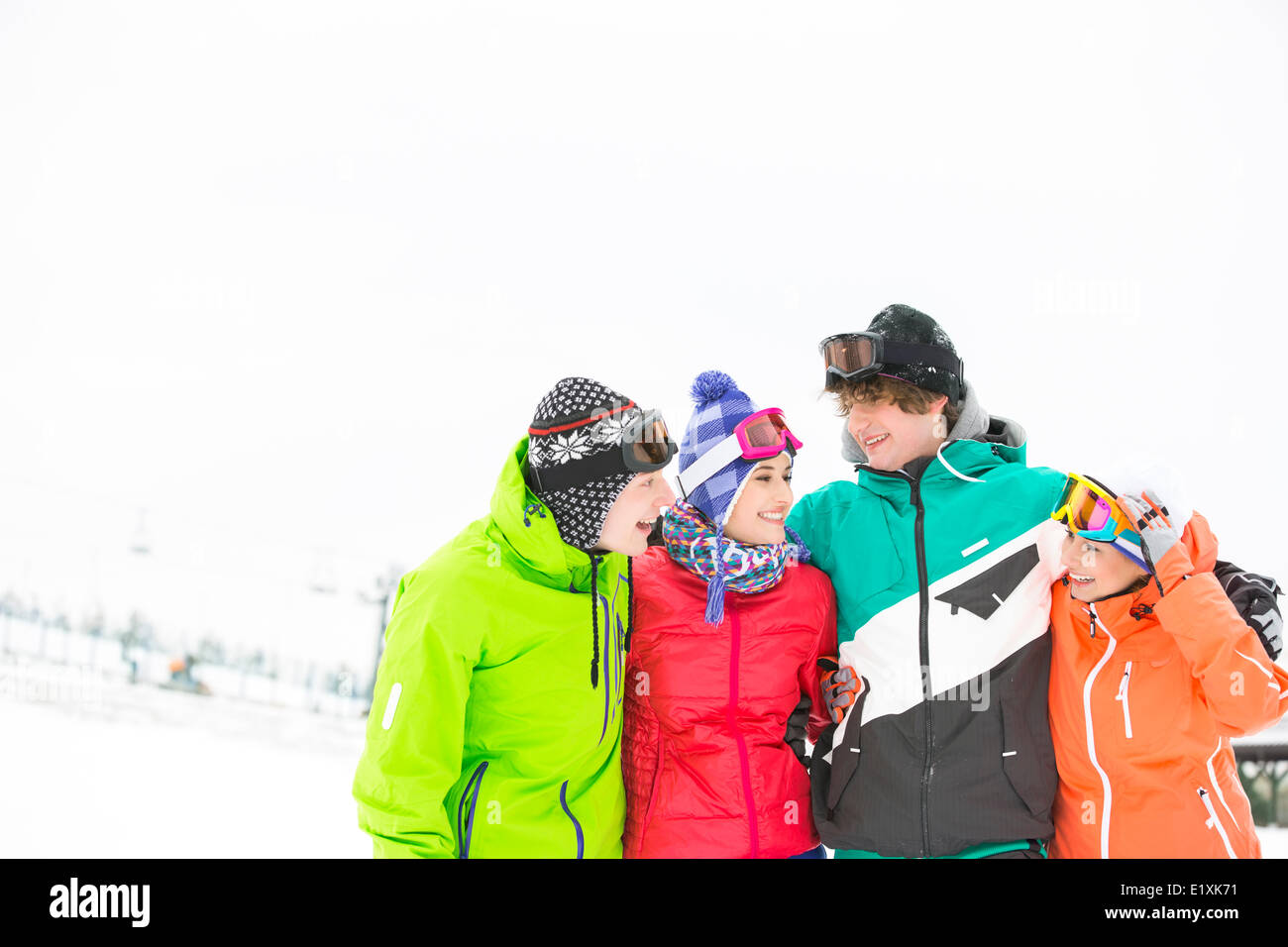 Cheerful young friends standing arm around in snow - Stock Image