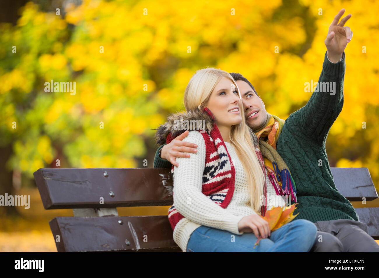 Young man showing something to woman while gesturing in park during autumn - Stock Image