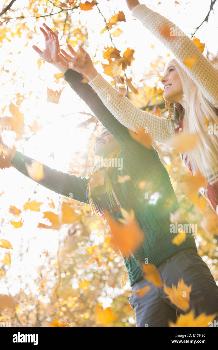 Couple with arms raised enjoying falling autumn leaves in park - Stock Image