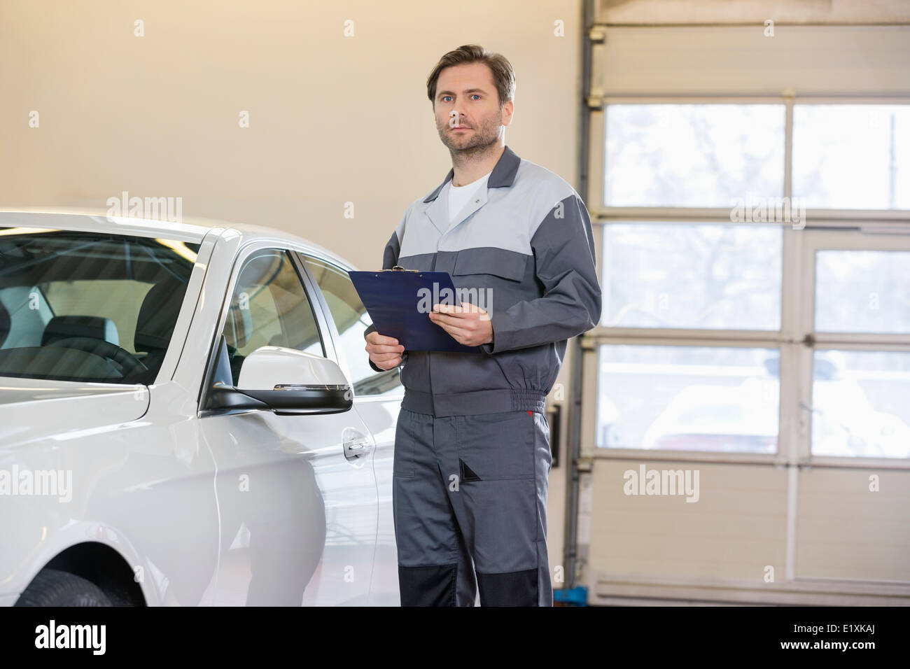 Portrait of confident male mechanic with clipboard standing by car in workshop Stock Photo