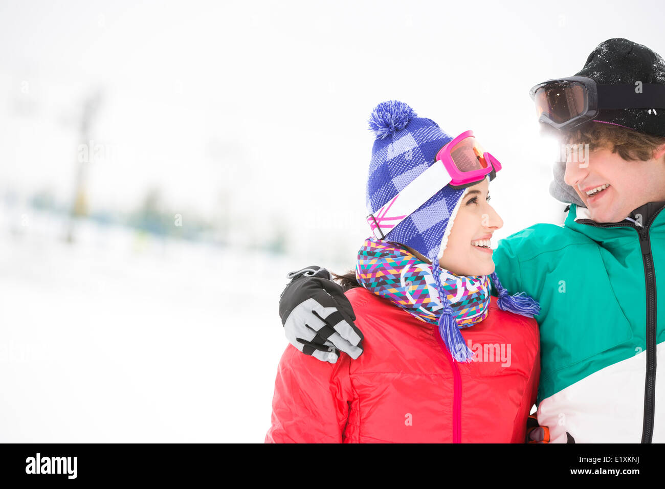 Loving young couple looking at each other in snow - Stock Image