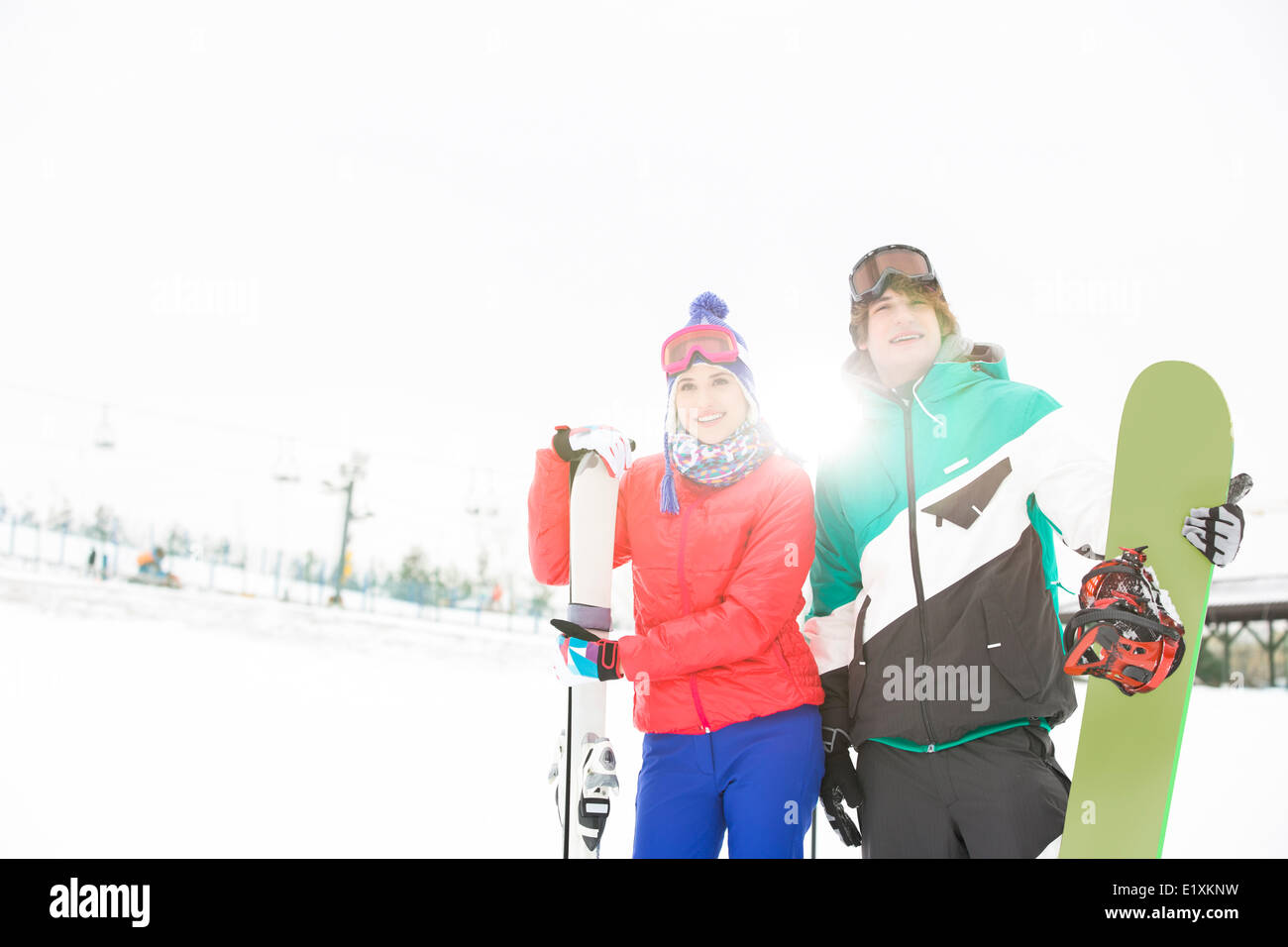 Young couple with snowboard and skis in snow - Stock Image