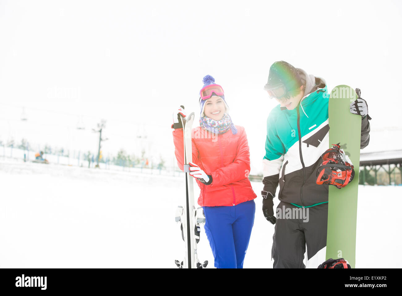 Happy young couple with snowboard and skis in snow - Stock Image