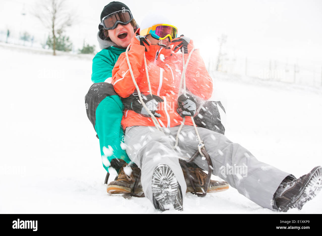 Excited young couple sledding in snow - Stock Image