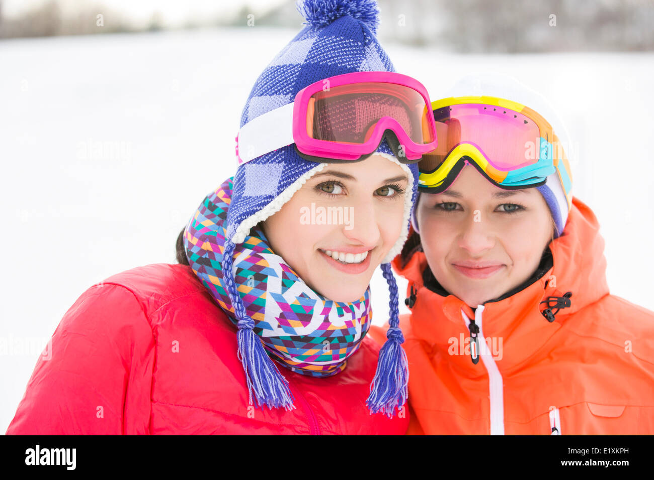 Portrait of happy young female friends in warm clothing outdoors - Stock Image
