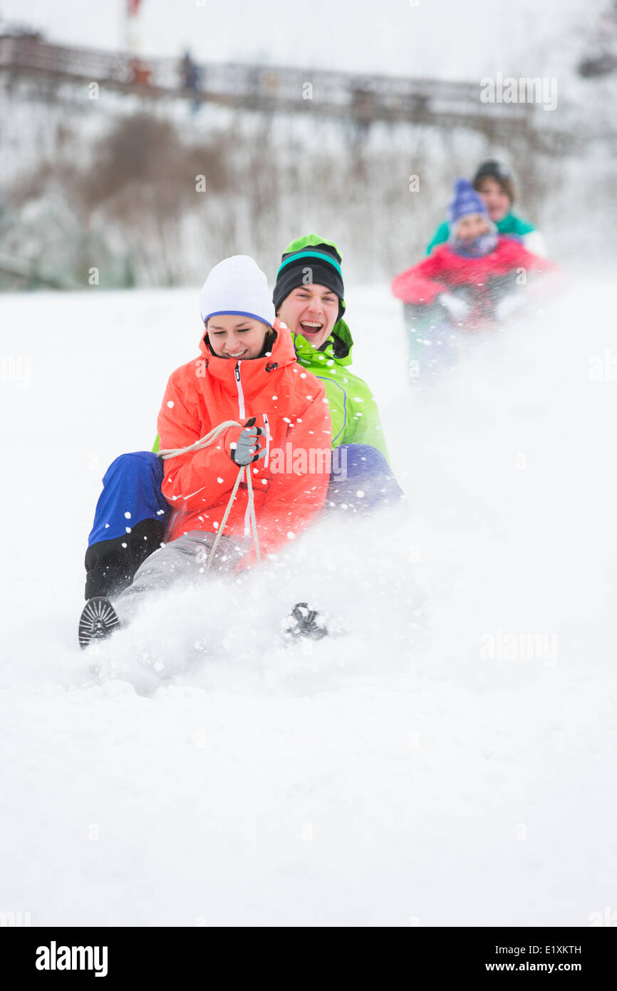 Young couple enjoying sled ride on snow covered slope - Stock Image