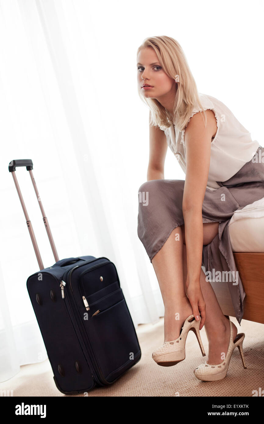 Portrait of beautiful young businesswoman removing high heels in hotel room - Stock Image