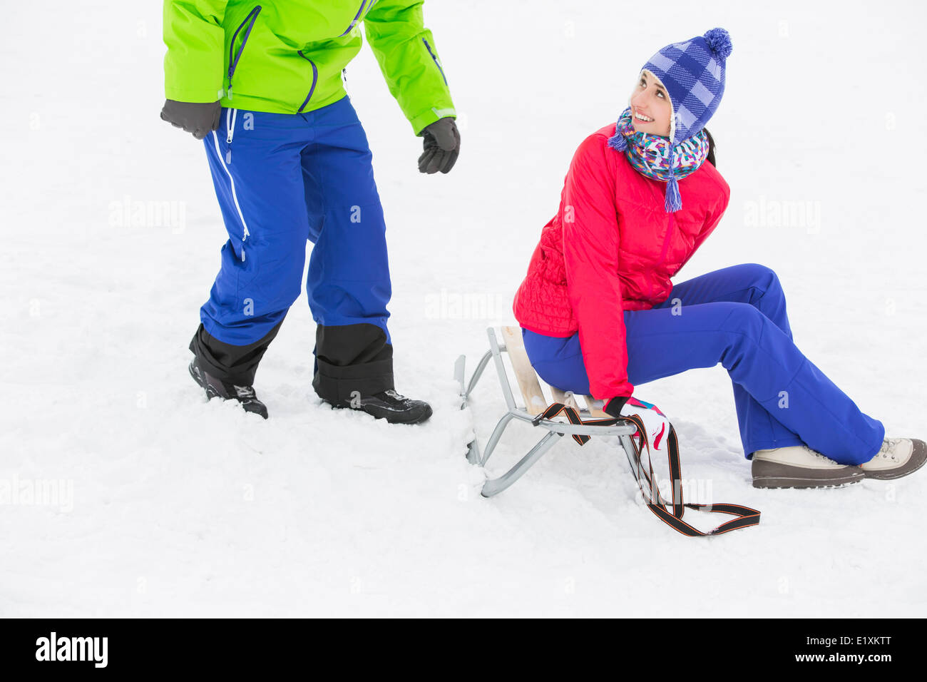 Happy young woman sitting on sled while looking at man in snow - Stock Image