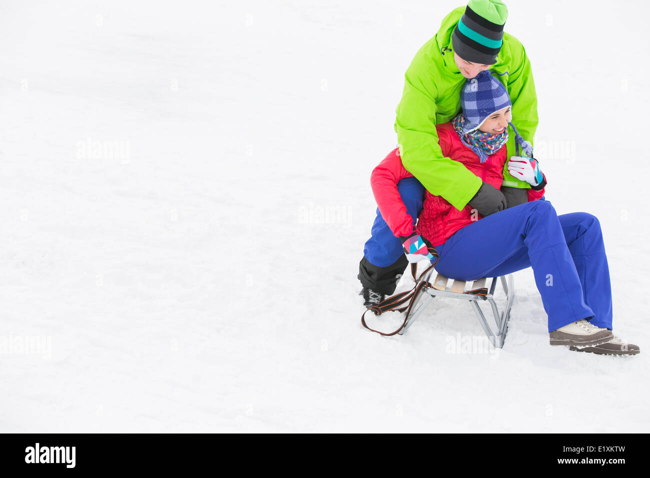 Young man embracing woman on sled in snow - Stock Image