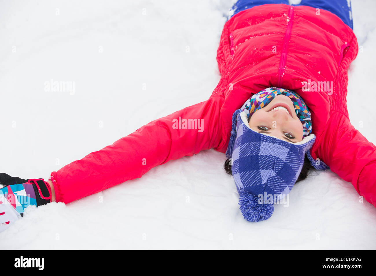 Portrait of smiling young woman lying on snow Stock Photo