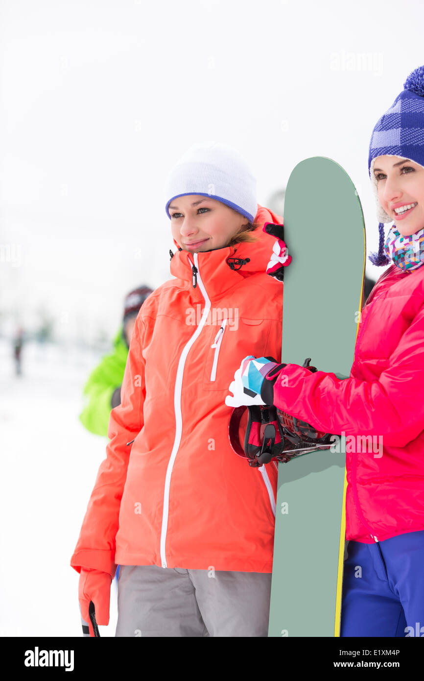 Beautiful young women with snowboard looking away - Stock Image