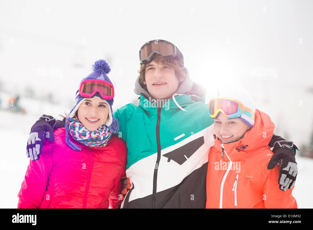 Happy young man with female friends standing arm around in snow Stock Photo