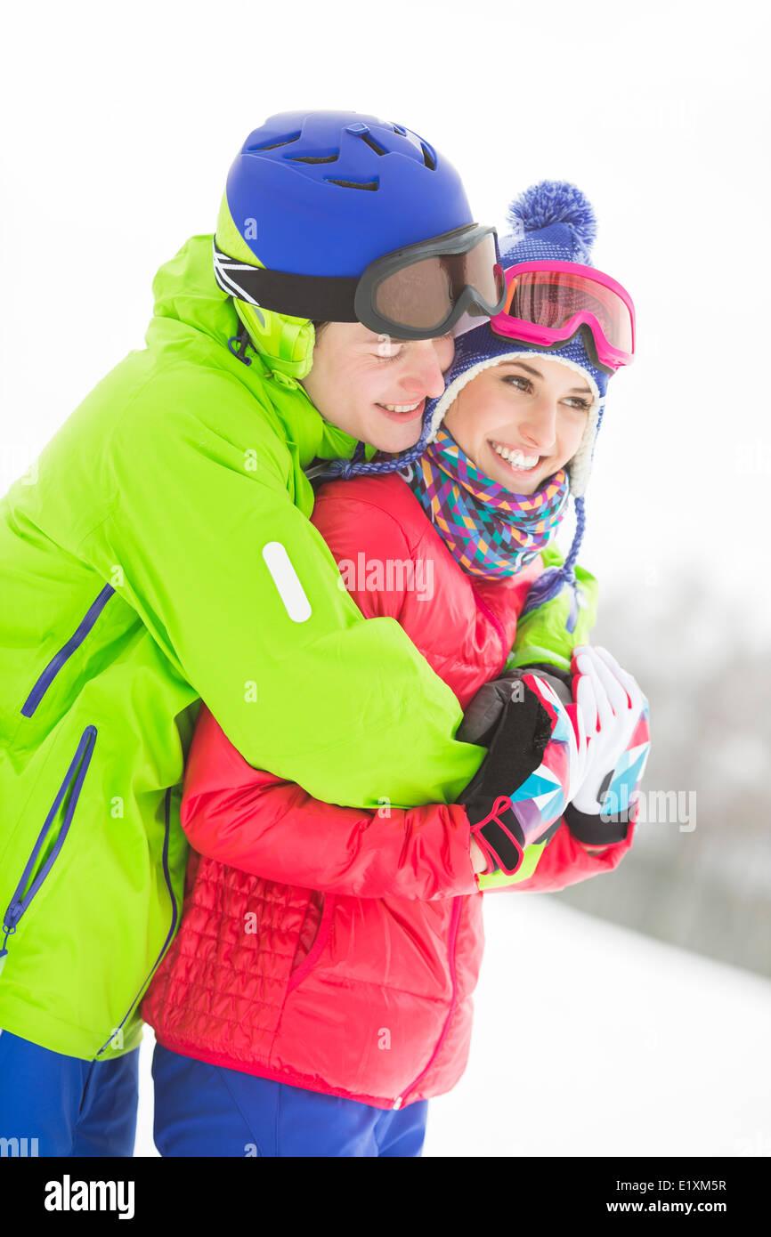 Happy loving man hugging woman in snow - Stock Image