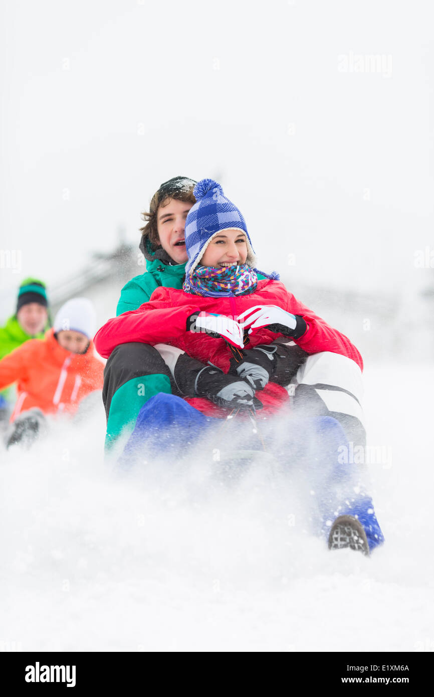 Excited young friends sledding in snow - Stock Image