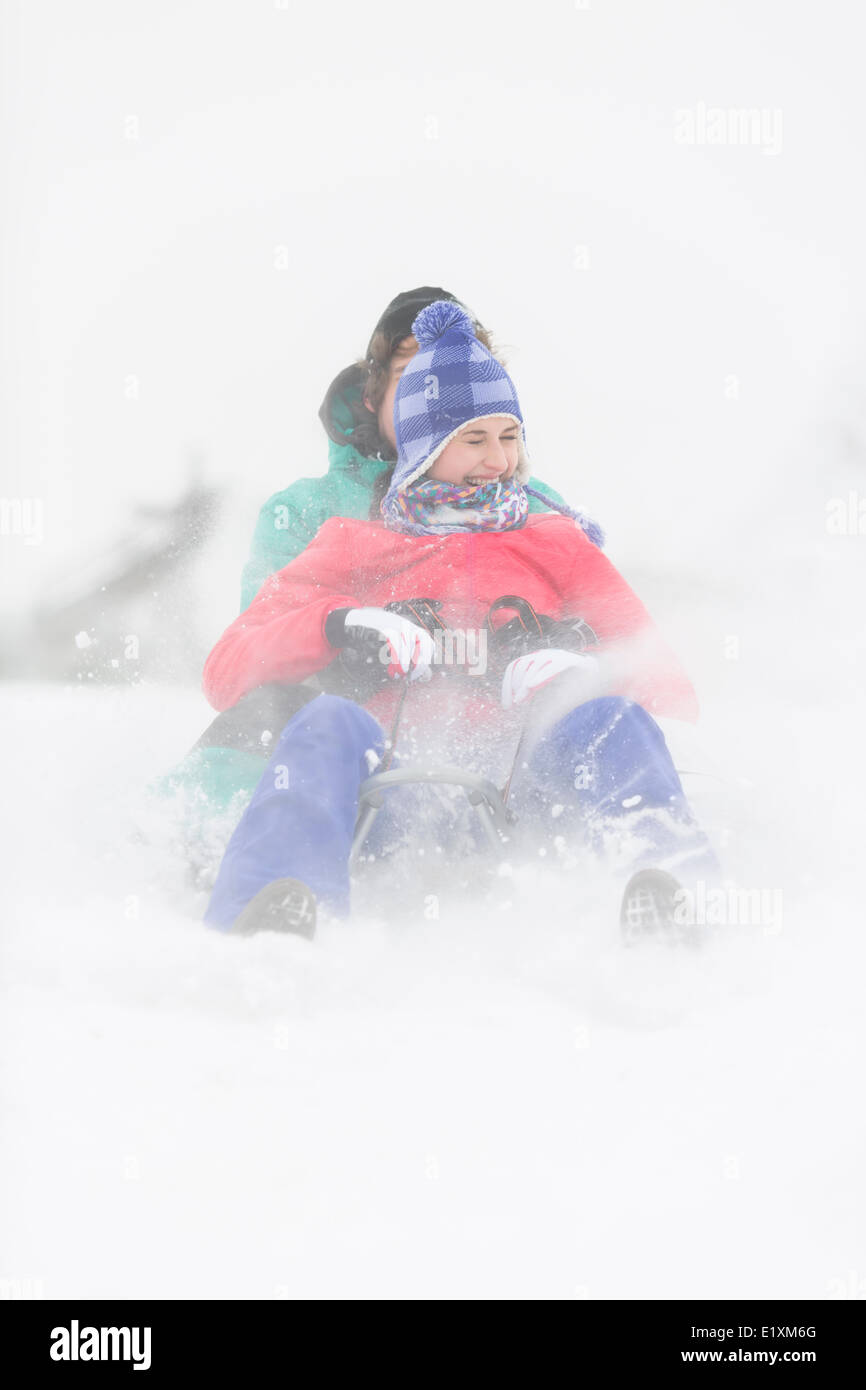 Cheerful young couple sledding in snow - Stock Image