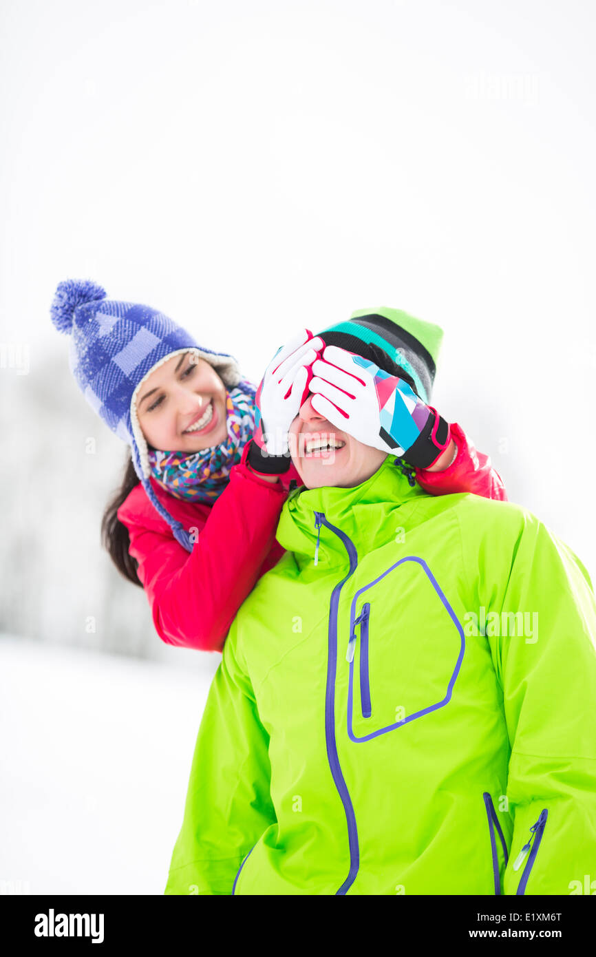 Smiling young woman covering man's eyes in winter - Stock Image