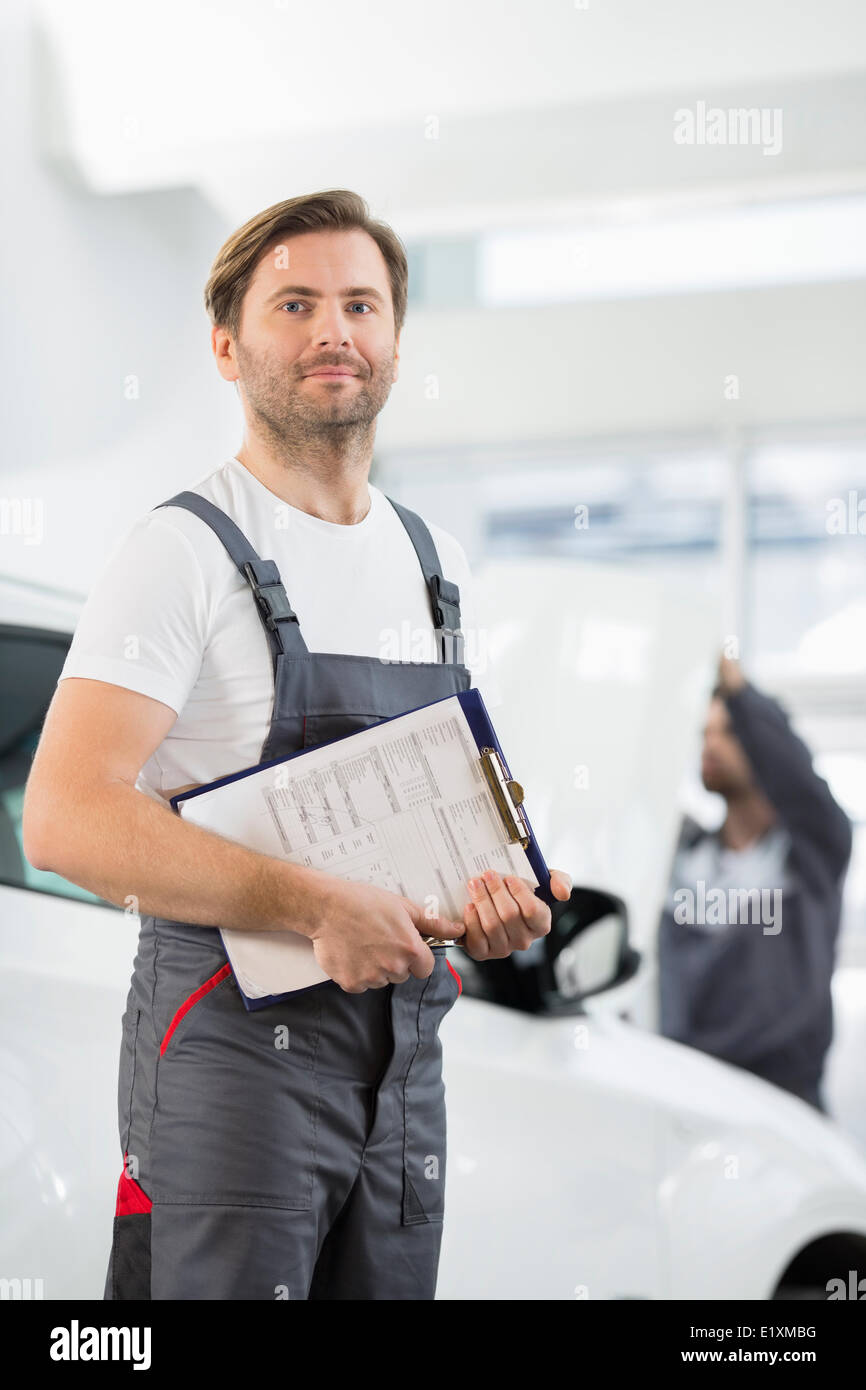 Portrait of confident male automobile mechanic with clipboard in car repair store Stock Photo