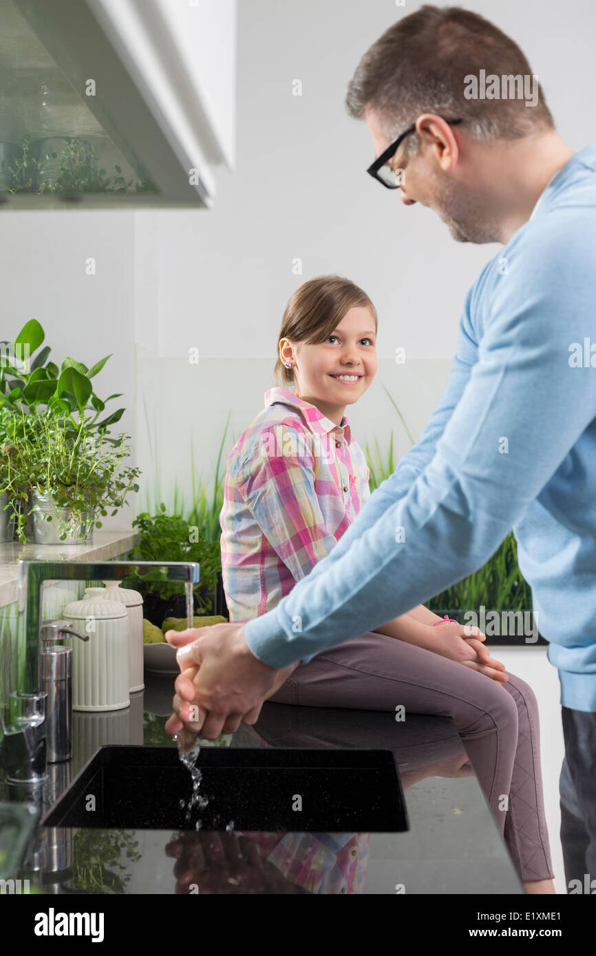 Smiling girl looking at father washing hands in kitchen - Stock Image