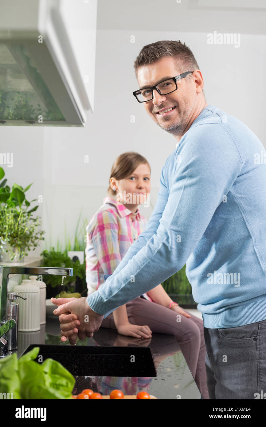 Portrait of smiling man washing hands with daughter sitting on counter in kitchen - Stock Image
