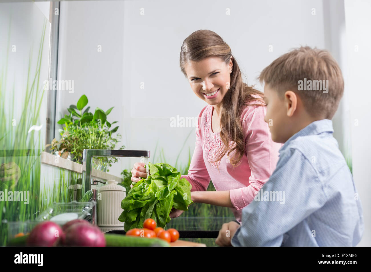 Happy mother and son washing vegetables in kitchen - Stock Image