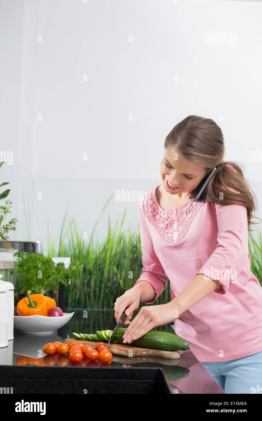 Smiling woman using cell phone while cutting cucumber at kitchen counter - Stock Image
