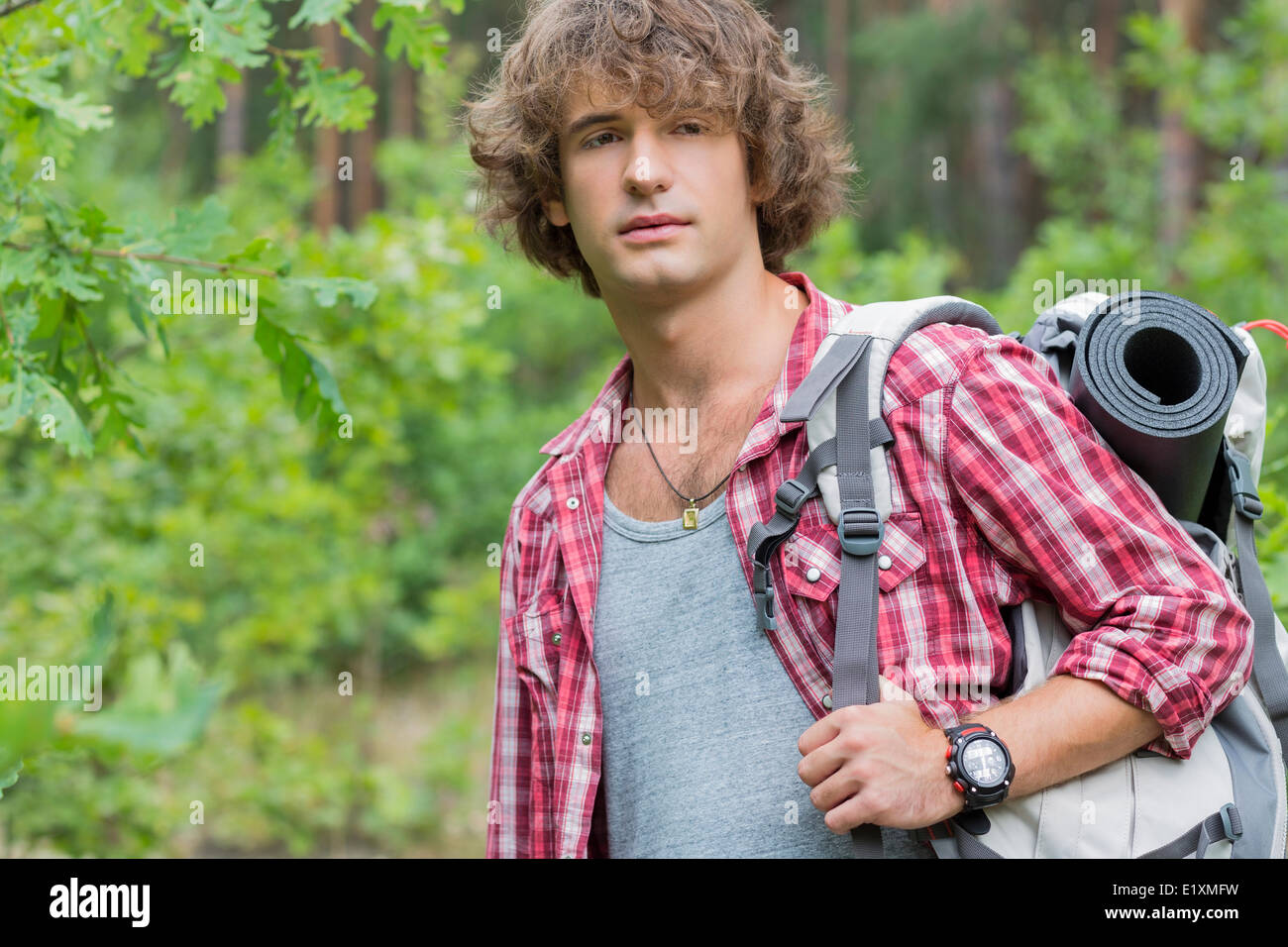 Young male hiker with backpack looking away in forest - Stock Image