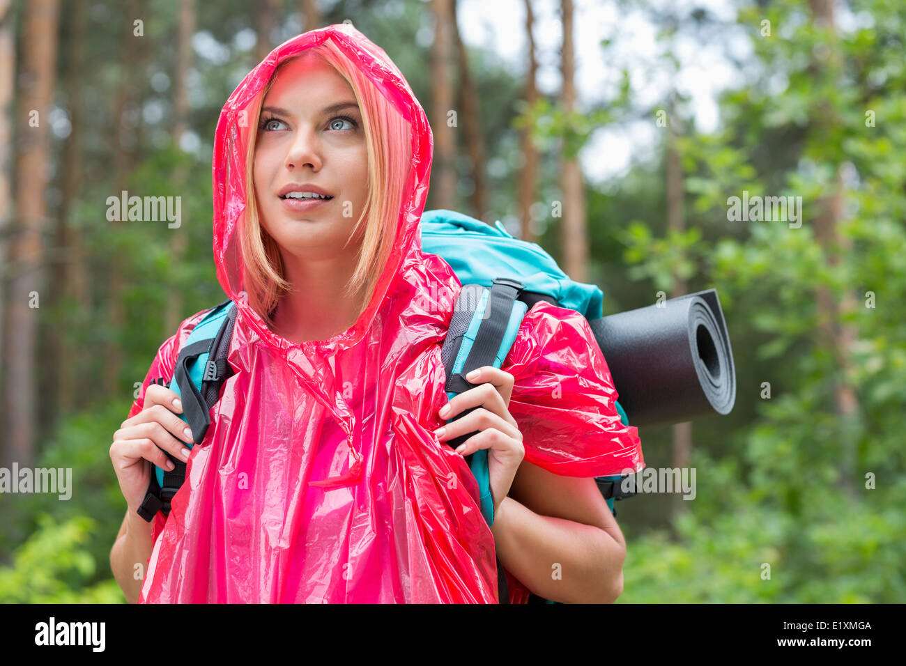 Beautiful backpacker in raincoat looking away at forest - Stock Image