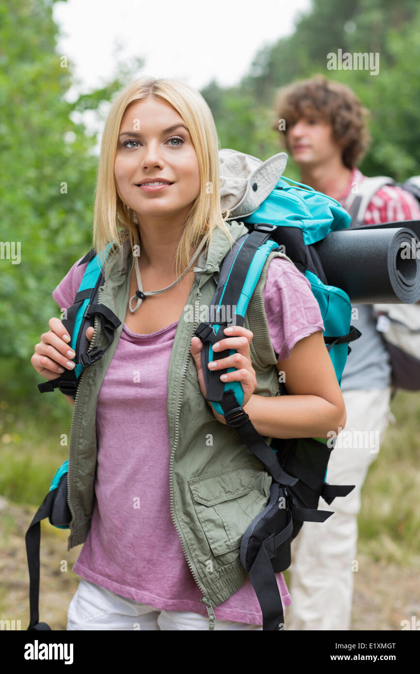 Beautiful female backpacker looking away with man standing in background at forest - Stock Image